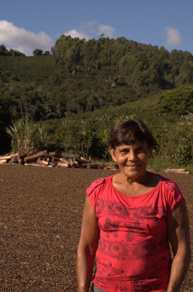 Dona Concepcao, on her coffee farm with her recently harvested coffee drying in the patio